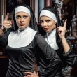 Attractive young nuns posing in the church — Stock Photo