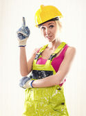 Female wearing coverall and hard hat posing indoors — Stock Photo