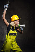 Attractive builder woman shouting through megaphone — Stock Photo