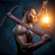 Muscular man holding pickaxe and oil lamp — Stock Photo #28074683