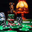 Gamble background, poker chips, cards and bottle of cognac — Stok fotoğraf