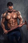 Muscular man holding pickaxe — Stock Photo