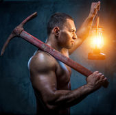 Muscular man holding pickaxe and oil lamp — Stock Photo