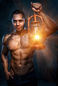 Muscular build man holding oil lamp — Stock Photo