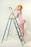 Sexy blonde woman wearing hard hat posing indoors — Stock Photo