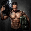 Muscular man with two metal fuel cans indoors — Stock Photo #28196071