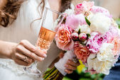 Beautiful bridal bouquet and glass of champagne — Stock Photo
