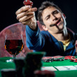 Stock Photo: Poker player holding poker chip