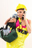Female construction worker with tool bag talking by phone — Stock Photo