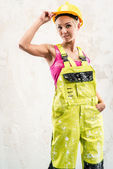 Female construction worker posing over white obsolete wall — Stock Photo