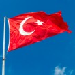 Waving flag of Turkey over blue sky background — Stock Photo #32311839