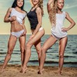 Three sexy young women posing on the beach — Stock Photo