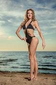 Sexy woman in black bikini posing on the beach — Stock Photo