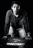 Young gambler indoors, black and white photo — Stock Photo