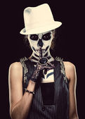 Woman with skeleton face art making a hush gesture — Stock Photo