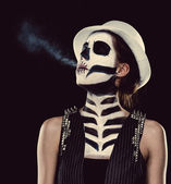 Woman with skeleton face art smoking — Stock Photo