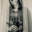 Day of the dead girl with sugar skull makeup holding rose — Stock Photo