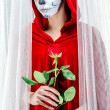 Day of the dead girl with sugar skull makeup holding red rose — Photo