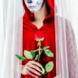 Day of the dead girl with sugar skull makeup holding red rose — Стоковое фото