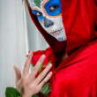 Day of the dead girl with sugar skull makeup holding red rose — Stock fotografie