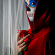 Day of the dead girl with sugar skull makeup holding red rose — Foto Stock #34292155