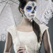 Day of the dead girl with sugar skull makeup holding lace umbrel — Stock Photo