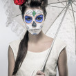 Stock Photo: Day of the dead girl with sugar skull makeup holding lace umbrel