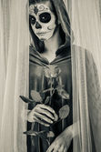 Day of the dead girl with sugar skull makeup holding rose — Stockfoto
