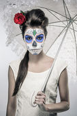 Day of the dead girl with sugar skull makeup holding lace umbrel — Stockfoto