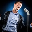 Man in elegant black jacket and blue shirt singing — Stock Photo