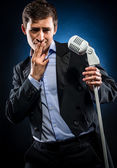 Man in elegant black jacket and blue shirt singing — Stockfoto