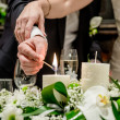 Bride and groom lighting a candle — Stock Photo