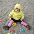 Lovely baby girl playing with plastic toy set on the beach — Stock Photo #39762849