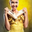 Foto Stock: Smiling ballerinin yellow tutu holding pointe shoes