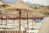 Parasols and empty deckchairs on the Nerja beach. Spain — Stock Photo