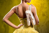 Ballerina with pointe shoes against obsolete wall background — Stock Photo
