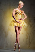 Beautiful ballerina in yellow tutu on point over obsolete wall — Stock Photo