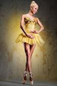 Beautiful ballerina in yellow tutu on point over obsolete wall — Stock Photo