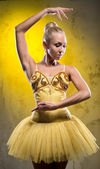 Lovely ballerina in yellow tutu posing over obsolete wall — Stock Photo