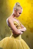 Sad ballerina in yellow tutu posing over obsolete wall — Stock Photo