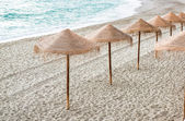 Straw parasols on empty beach. Nerja, Spain — Stock Photo