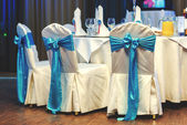 White wedding chairs decorated blue bows at restaurant — Stock Photo