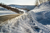 Snowdrifts and rural road — Stock Photo