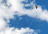 Airplane over cloudy sky background — Stock Photo