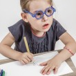 Cute Little Girl with Blue Glasses Painting on a School Desk — Stock Photo #36044267