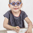 Cute Little Girl with Blue Glasses Painting on a School Desk — Stock Photo #36045707