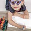 Cute Little Girl with Blue Glasses Painting on a School Desk — Stock Photo