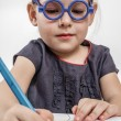 Cute Little Girl with Blue Glasses Painting on a School Desk — Stock Photo #36051739