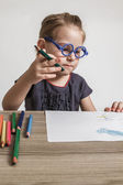 Cute Little Girl with Blue Glasses Painting on a School Desk — Stockfoto