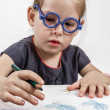 Cute Little Girl with Blue Glasses Painting on a School Desk — ストック写真
